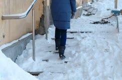 Скользкие лестницы Непознаваемая женщина в сини вниз с куртки идя вверх по снежной лестнице стоковое фото