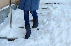 Скользкие лестницы Ноги женщины крупного плана в сини вниз с куртки идя вниз со снежной лестницы стоковые изображения rf