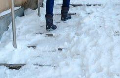 Скользкие лестницы Ноги женщины крупного плана в сини вниз с куртки идя вверх по снежной лестнице стоковые фото