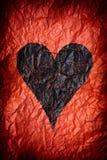 Скомканная красная бумага с черным сердцем Стоковые Фото
