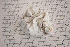 Скомканные бумажные шарик и вопросительные знаки на листе выровнянной бумаги Стоковые Фотографии RF