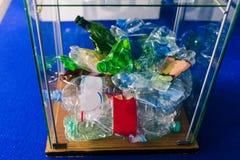 Скомканные пластиковые бутылки в стеклянной урне Куча скомканных пластиковых бутылок Проблема повторно использовать Повторно испо стоковые изображения
