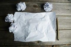 Скомканный вверх по бумагам с листом чистого листа бумаги и карандаша на серой деревянной предпосылке Стоковое Фото