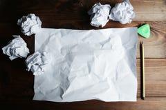 Скомканный вверх по бумагам с листом чистого листа бумаги и карандаша на коричневой деревянной предпосылке Стоковые Изображения