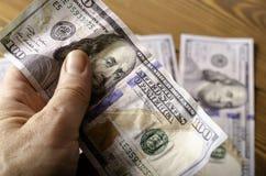 Скомканный конец-вверх банкноты $ 100 в руке над счетами $ 100 Стоковые Фото