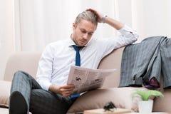 сконцентрированная газета чтения бизнесмена на софе Стоковые Изображения