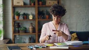 Сконцентрированная девушка режет часть красочной бумаги используя ножницы после этого кладя ее в тетрадь делая коллаж и акции видеоматериалы
