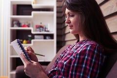 Сконцентрированная девушка с ручкой в руке делая учебную программу и планы Стоковые Фотографии RF