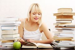 Сконцентрированная женщина сидя с стогом книг Стоковые Фото