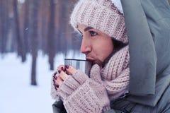 Сконцентрированная женщина смотря прямой пока наслаждающся горячей чашкой te Стоковые Изображения