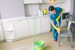 Сконцентрированная и трудолюбивая девушка работает в кухне Она смотрит вниз и стул чистки с оранжевой ветошью Зелено стоковое фото