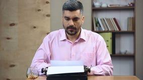 Сконцентрированная книга автора стар-школы печатая на винтажной машинке в его офисе видеоматериал