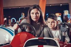 Сконцентрированная мать и сын управляя автомобилем игрушки стоковое изображение