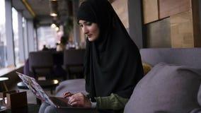 Сконцентрированная молодая мусульманская женщина работая на современном ноутбуке в кафе Привлекательная женщина в hijab держа ноу акции видеоматериалы