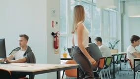 Сконцентрированная работа женщины заканчивая в coworking Серьезный фрилансер с тетрадью акции видеоматериалы