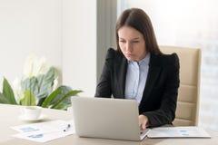 Сконцентрированная серьезная коммерсантка делая отчет, работая с l Стоковые Фотографии RF