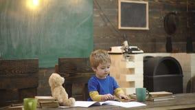 Сконцентрированное сочинительство ребенк в тетради с прописями Мальчик Preschool сидя на столе Учить письма в детском саде Мальчи акции видеоматериалы