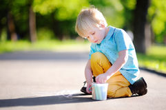Сконцентрированное усаживание и чертеж мальчика маленького ребенка с покрашенным мелом на асфальте Стоковые Изображения