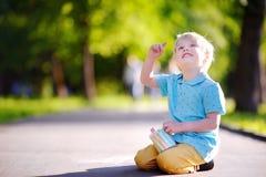 Сконцентрированное усаживание и чертеж мальчика маленького ребенка с покрашенным мелом на асфальте Стоковая Фотография
