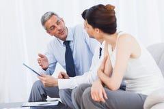 Сконцентрированные бизнесмены говоря о файлах на софе Стоковое Изображение RF