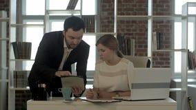 Сконцентрированные бизнесмены используя цифровую таблетку в встрече на офисе Стоковые Изображения RF