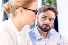 Сконцентрированные бизнесмен и коммерсантка при eyeglasses работая в офисе Стоковое фото RF