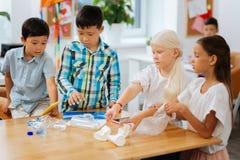 Сконцентрированные дети делая их домашнюю работу все вместе стоковые фотографии rf