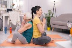Сконцентрированные женщины делая йогу дома Стоковое Изображение