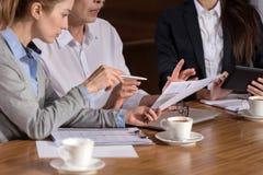 Сконцентрированные коллеги обсуждая отчет в офисе Стоковое Изображение