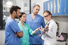Сконцентрированные коллеги обсуждая работу в лаборатории Стоковые Фото