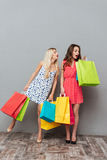 Сконцентрированные молодые дамы держа хозяйственные сумки Стоковое Фото