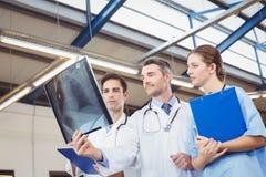 Сконцентрированные доктора рассматривая рентгеновский снимок Стоковые Изображения