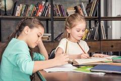 Сконцентрированные одноклассники делая домашнюю работу совместно в библиотеке Стоковые Фотографии RF