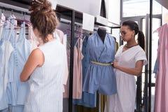 Сконцентрированные прозодежды женского портноя улучшая в выставочном зале стоковая фотография rf