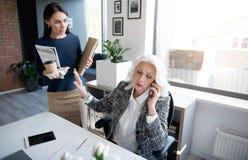 Сконцентрированные unsmiling женщины работают в офисе Стоковое Изображение