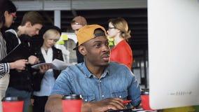 Сконцентрированный афро американский человек в случайной одежде работая на компьютере, получая непредвиденную электронную почту п акции видеоматериалы
