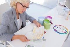 Сконцентрированный белокурый дизайнер по интерьеру держа диаграммы цвета Стоковая Фотография