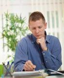 Сконцентрированный бизнесмен анализируя данные в его офисе Стоковая Фотография RF