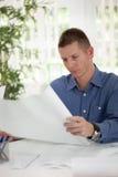 Сконцентрированный бизнесмен анализируя диаграммы в его офисе Стоковое фото RF