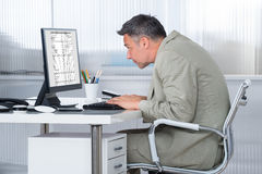 Сконцентрированный бизнесмен используя компьютер на столе Стоковая Фотография