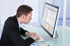 Сконцентрированный бизнесмен работая на компьютере в офисе Стоковые Изображения