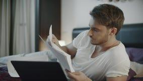 Сконцентрированный бизнесмен работая с рабочим местом бумаг дома на вечере сток-видео