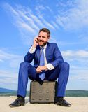 Сконцентрированный бизнесмен сидит на предпосылке голубого неба портфеля решение принципиальной схемы проверки дела коробки отсут стоковое фото