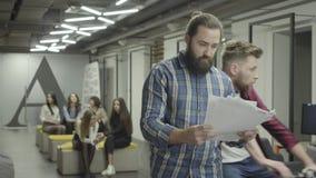 Сконцентрированный бородатый человек изучая документы бумаг стоя в офисе Молодой коллега ехать велосипед в офисе акции видеоматериалы