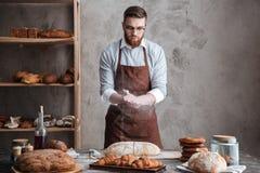 Сконцентрированный детенышами хлебопек стекел бородатого человека нося стоковое изображение rf