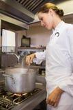 Сконцентрированный женский кашевар подготавливая еду в кухне Стоковые Изображения RF