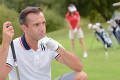 Сконцентрированный игрок в гольф принимая съемку на поле для гольфа стоковое фото rf