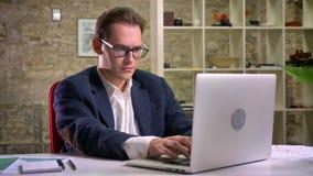 Сконцентрированный кавказский мужчина сидящ и смотрящ его работая компьтер-книжка и после этого на ослабленная камера на предпосы акции видеоматериалы