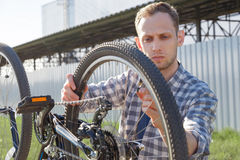 Сконцентрированный мастер диагностирует неисправности велосипеда на улице Стоковое фото RF