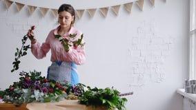 Сконцентрированный молодой женский флорист создавая флористический состав, проверяет цветки стоковое изображение rf